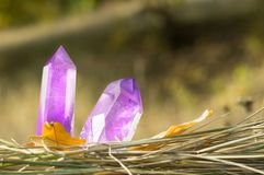 A large transparent mystical faceted crystal of colored purple lilac amethyst, chalcedony on nature blurred background close-up. stock photography