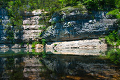 Large Cliff reflecting Arkansas Calm River. Arkansas Green State Lake Beauty with lush green shrub and forests throughout the Ozark Mountain valley and royalty free stock image