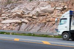 Large cliffs with trucks. Close-up Truck is blurring on a sloping street along a mountain shoulder near a large rocky cliff Royalty Free Stock Photo
