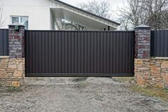 Large closed brown gates and part of the fence in the street stock photos
