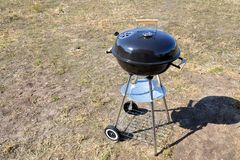 Large closed round grill with a thermometer. Grill on wheels stock image