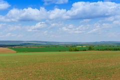 Large clouds over Cultivated field in countryside Royalty Free Stock Images