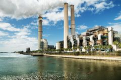 A large coal-fired power plant in Tampa and dozens of manatees b Stock Photos