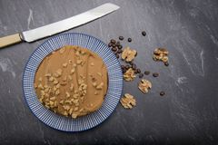Large coffee and walnut cake on a dark background Royalty Free Stock Images
