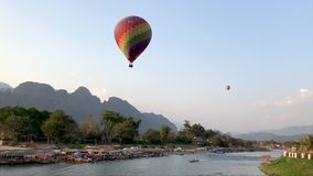 A large colorful balloon flies over the river in Laos.