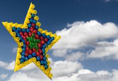 Large colorful star of differently colored lamps exempted in front of a blue sky with clouds royalty free stock photography