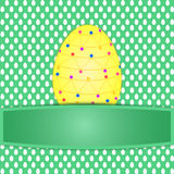 Large colorful yellow easter egg on easter egg pattern Stock Images