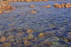 Large Coloured Rocks, under and Above the Ocean, Danger to mooring Boats. Small ocean cove with a rocky shore line. Coloured Rocks, under and Above the Ocean royalty free stock images