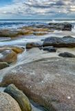 Large colourful rocks in shallow sea water soft waves blue sky with clouds. Queensland Australia stock photos
