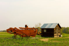 A large combine beside a small cabin Royalty Free Stock Photography