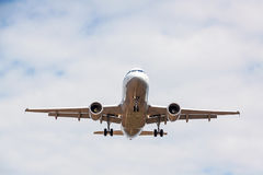 Airplane flying overhead - landing / takeoff - blue sky with clouds Royalty Free Stock Images
