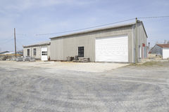 Large commercial garage. With one door which is closed.  The structure is by a gravel parking area Royalty Free Stock Photo