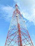 Large communications tower antenna. A large tower antenna, with microwave antennas built into it. Painted red and white for visibility. Blue sky with some clouds stock photo