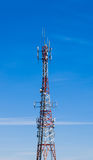 Large communications tower on blue sky. Stock Photo