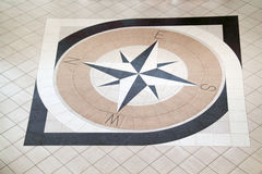 Large compass on floor. Large compass inlaid with black and light brown tiles on floor Stock Photo