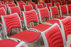 Empty red seats. A large concert hall full of emty red seats Stock Photos