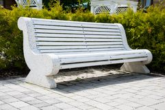 Large concrete benches with wooden elements. Near the alley in the park. Summer in the yard. Summer day. Large concrete benches with wooden elements. Next to stock image