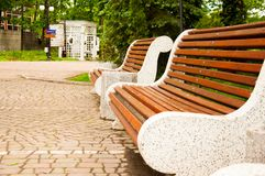 Large concrete benches with wooden elements. Near the alley in the park. Summer in the yard. Summer day. Large concrete benches with wooden elements. Next to stock photography