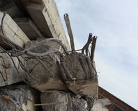 Large concrete chunks with twisted metal and industrial building Stock Image