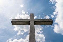 A large concrete cross on a cemetery against a blue sky with white clouds. A large concrete cross on a cemetery against a blue sky with white clouds royalty free stock photos