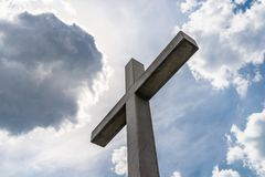 A large concrete cross on a cemetery against a blue sky with white clouds. A large concrete cross on a cemetery against a blue sky with white clouds stock photo