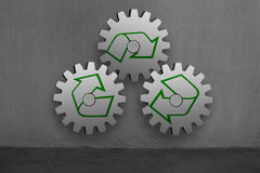 3 large concrete gears with recycle mark hanging on concrete wal Royalty Free Stock Image