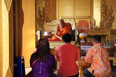 Old Buddhist monk blessing a family  Royalty Free Stock Image