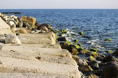 Large concrete rectangular blocks to protect the shore from erosion lie in the sea. Enclosure of railroad tracks Stock Image