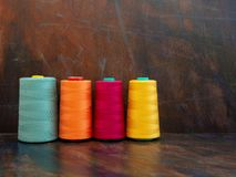 Large professional industrial cones of colorful sewing threads laying and standing on a dark background. Front view studio shot. Large cones of industrial royalty free stock photography
