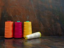 Professional industrial cones of colorful sewing threads laying and standing on a dark background. Front view studio shot. Large cones of industrial sewing royalty free stock photo