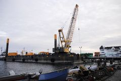 Construction barge constructing. A large construction barge revamping a Mackinac Island pier during the off season stock images