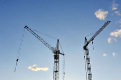 Large construction crane against the blue sky. Silhouette Stock Image