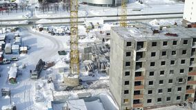 A large construction crane carries a concrete slab near the unfinished building during the winter. The view from the. Heights on the construction process of stock video footage