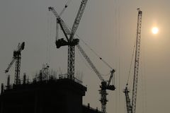 Large construction cranes are building high-rise buildings in th. E evening,Picture of silhouette style Stock Images