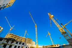 Large construction cranes. High and heavy construction machinery. Construction of  houses. Urbanization is the process of urban growth Stock Images