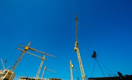 Large construction cranes. High and heavy construction machinery. Construction of  houses. Urbanization is the process of urban growth Royalty Free Stock Photo