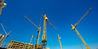 Large construction cranes. High and heavy construction machinery. Construction of  houses. Urbanization is the process of urban growth Stock Photos
