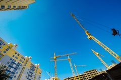 Large construction cranes. High and heavy construction machinery. Construction of  houses. Urbanization is the process of urban growth Stock Image