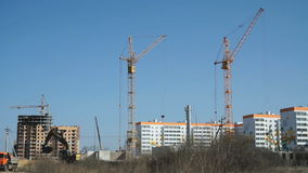Large construction cranes work on construction stock video footage