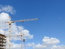 Large construction site, including several cranes working on the construction complex, with a clear blue sky. City industry business architecture estate build stock photo