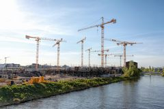 Large construction site with many cranes on a river, on a sunny, hazy day - Berlin 2018. A large construction site with many cranes on a river, on a sunny, hazy stock photography