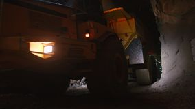 Large construction trucks working inside a tunnel. Work site stock video footage