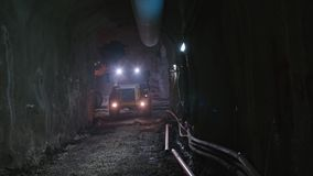 Large construction trucks working inside a tunnel. Work site stock footage