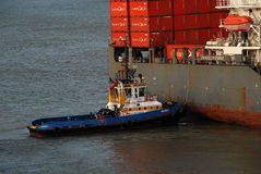 A large Container ship being gently pushed to a dock at the Cartagena Harbor Stock Photography