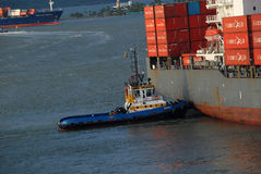 A large Container ship being gently pushed to a dock at the Cartagena Harbor Royalty Free Stock Photography