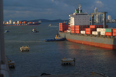 A large Container ship being gently pushed to a dock at the Cartagena Harbor Stock Photo