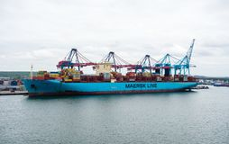 Large container ship docked near cranes. Royalty Free Stock Photos