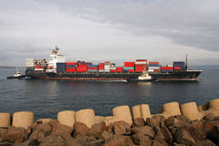 Large container ship entering harbour Royalty Free Stock Photo