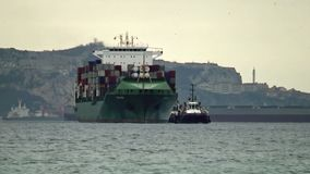 Large container ship entering in the port of Algeciras. Early in the morning the big containership Barbara and various tugs vessels enter in Algeciras port stock video