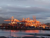 Large container terminal glistens in late afternoon sunlight in Vancouver harbor. Cranes in a major container terminal are illuminated by late afternoon sunrays royalty free stock image